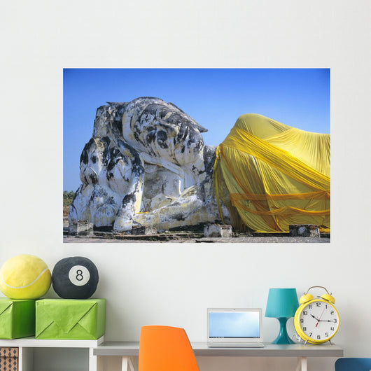 Reclining Budda statue wrapped with yellow cloth Wall Mural