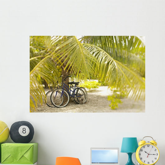 French Polynesia, Tuamotu, Palm Tree With Two Bikes Leaned Against It Wall Mural