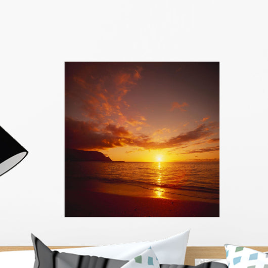 Calm Shoreline Ocean Waters With Orange Reflections From Sunset Wall Mural