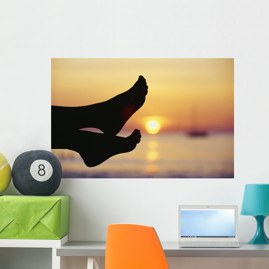 Silhouette Of Feet In Front Of A Sunset Over The Ocean Wall Mural