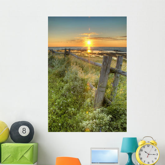 Sunset Over Water And A Fence Along The Shoreline Wall Mural