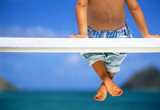 Hawaii, Legs And Feet Of Young Boy Sitting On A Bench By The Ocean Wall Mural