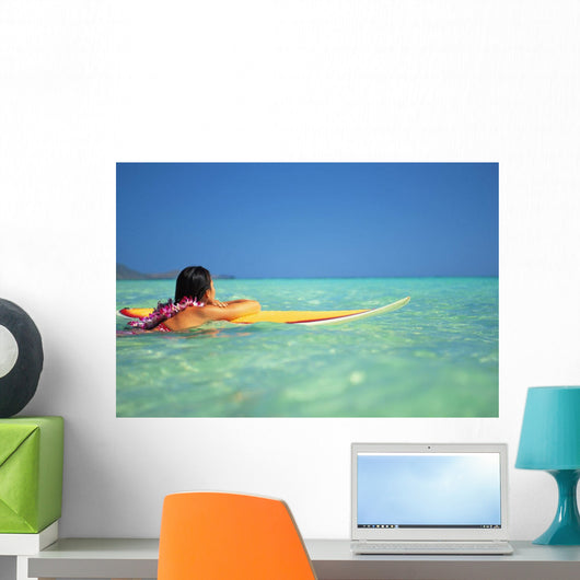 Woman Resting On Surfboard Looking Out On Clear Teal Water Wall Mural