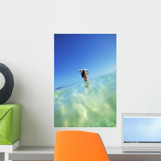 Over/Under View Of Woman Holding Surfboard On Head Wall Mural