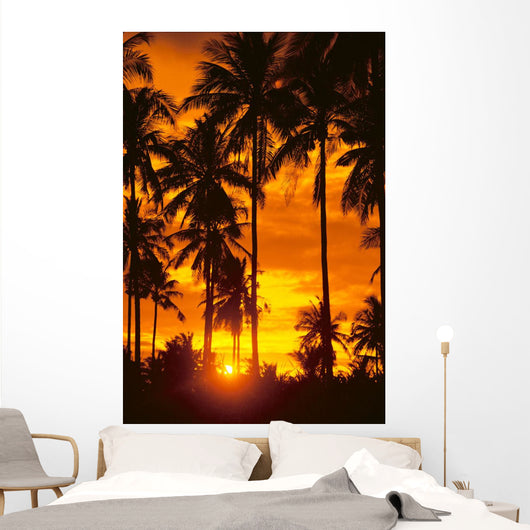 Many Palms Silhouetted In Vibrant Orange Sunset Sky Wall Mural