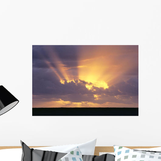 Sunrays Stream Out From Behind Clouds At Sunset, Over Dark Ocean Wall Mural
