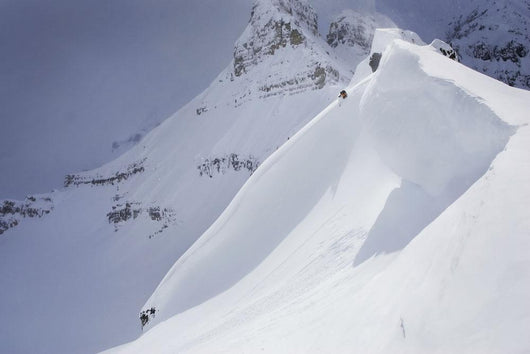Skier On Crest Of Big Drop, Dwarfed By Mountain Wall Mural