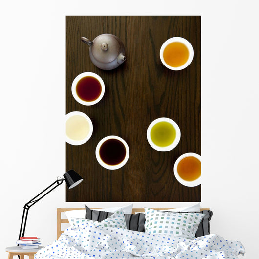 Teapot And Different Types Of Tea In Cups On A Wood Table Wall Mural