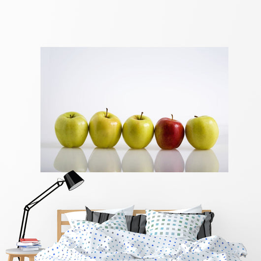 Four Yellow Apples With One Red Apple In A Row On A Reflective Surface Wall Mural