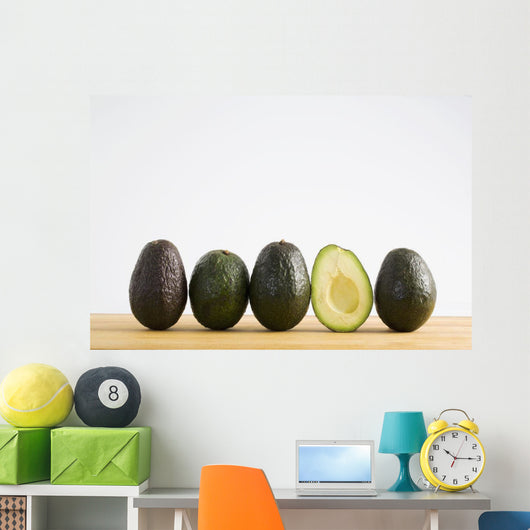 A Row Of Avocados Standing Upright On A Wooden Board With One Cut Wall Mural