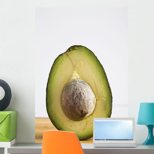 Close Up Of An Avocado Standing Upright Cut In Half With The Pit Wall Mural