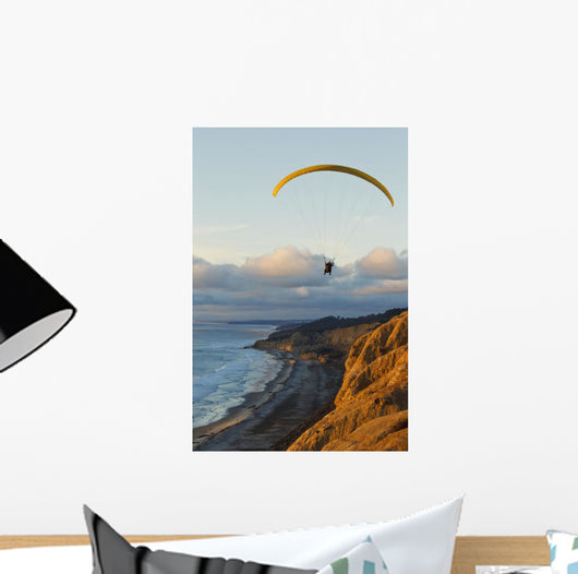 Paraglider flying over ocean cliffs at sunset EDITORIAL USE ONLY Wall Mural