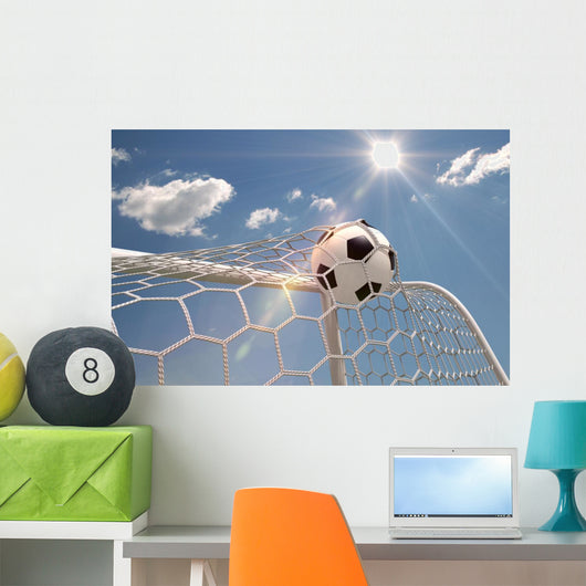 Soccer ball in the net on the sky background Wall Mural