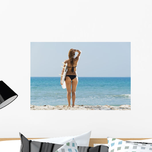 A woman wearing a black bikini stands Wall Mural