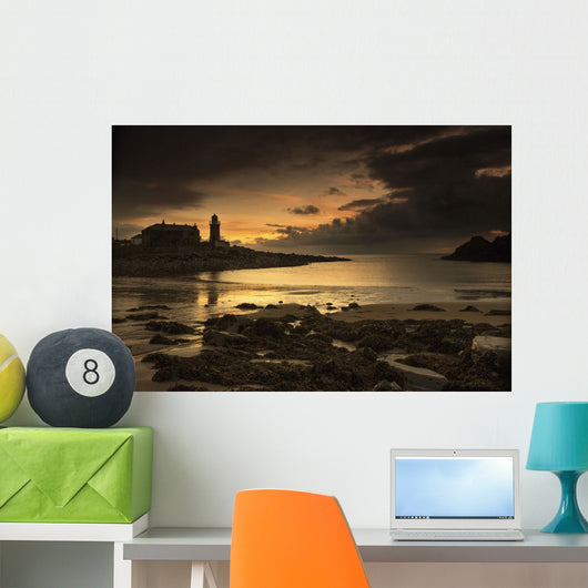 Silhouette of a lighthouse along the coast Wall Mural