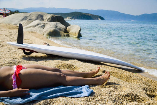 Young woman sunbathing on beach with surf board on sand Wall Mural