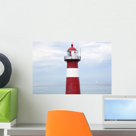 Red and white lighthouse along the coast with a sailboat Wall Mural