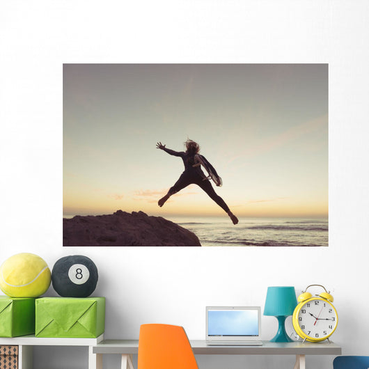 Spain, Andalusia, Cadiz, Costa de la Luz, Surfer jumping from rock Wall Mural