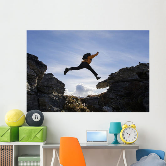 Hiker Leaps Between Rocks Near Noatak River In The Brooks Range Wall Mural