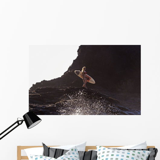 Distant View Of Female Surfer With Surfboard Standing On Rock Wall Mural
