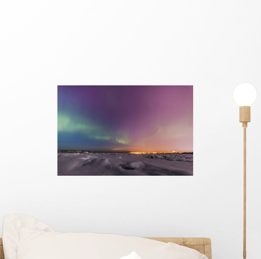 Northern lights shine above city skyline in this nighttime view Wall Mural
