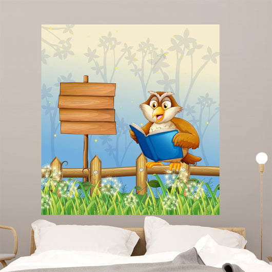 An owl reading a book beside a wooden signboard Wall Mural