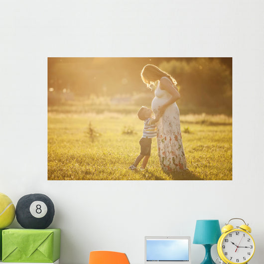 Small boy kissing belly of his pregnant mother outdoors Wall Mural