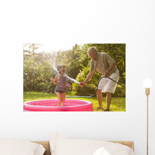 Grandparent and grandkid playing with hose Wall Mural