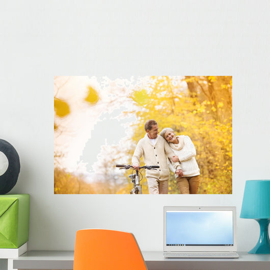 Senior couple with bicycle in autumn park Wall Mural