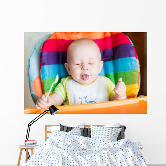 Adorable baby eating in high chair Wall Mural