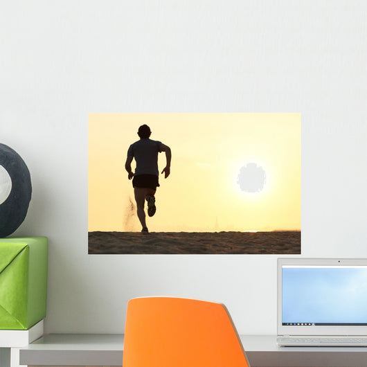 Back view silhouette of a runner man running on the beach Wall Mural