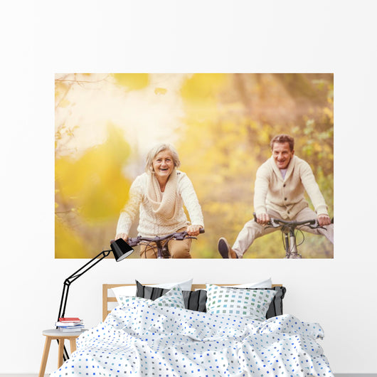 Active seniors ridding bike and having fun Wall Mural