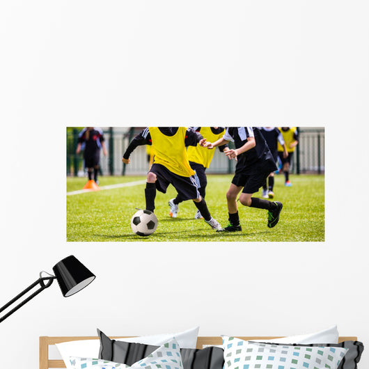 Football match for children. Boys playing football Wall Mural