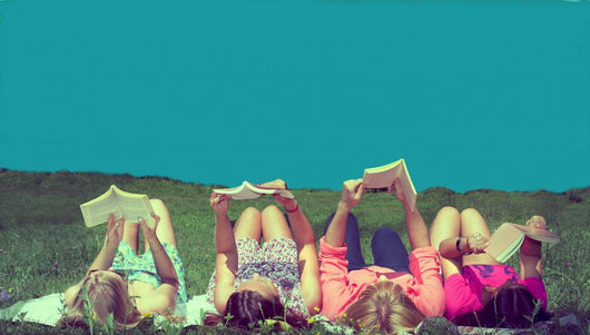 friends reading under sunshine lying on the meadow Wall Mural