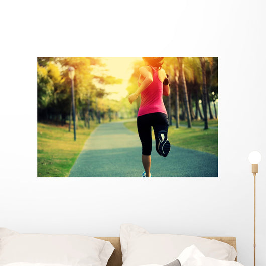 woman runner running at tropical park Wall Mural
