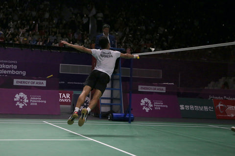 A person Anthony Ginting hitting a shuttle with a badminton racket on a court