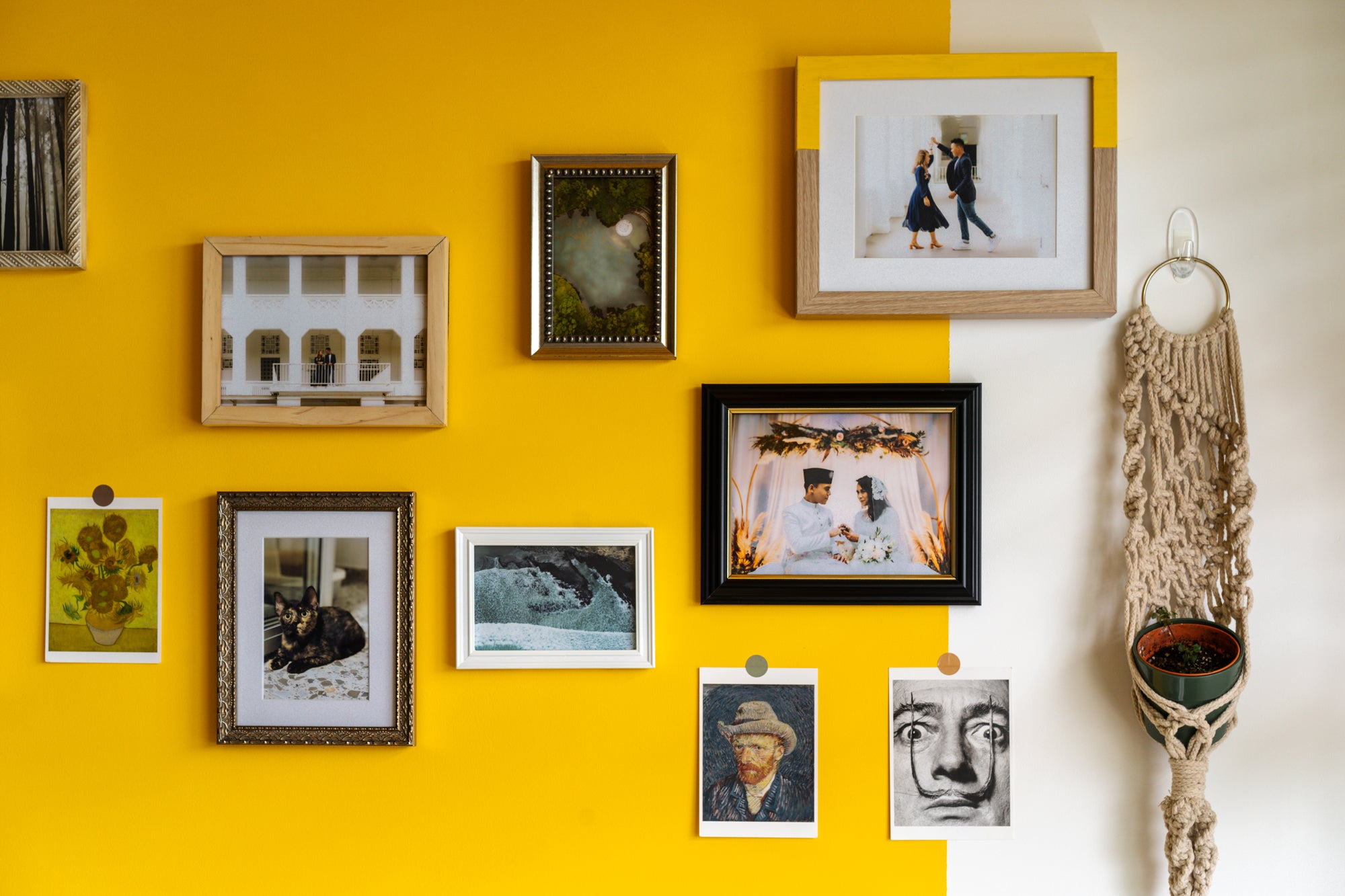 yellow wall filled with hanging photo frames and art
