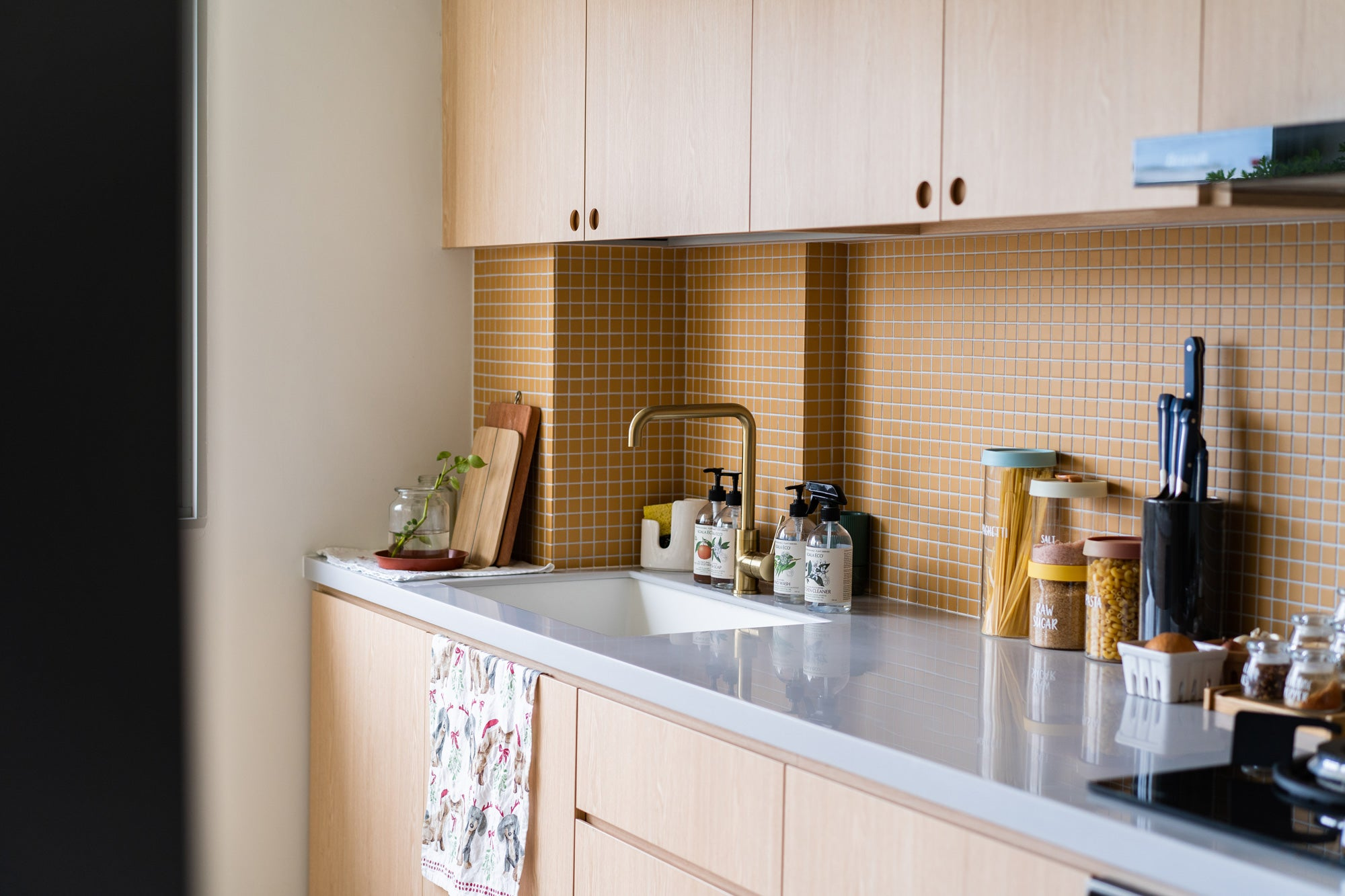 wooden kitchen cabinets with yellow backsplash tiles