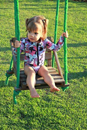 Little Girl on a swing  wearing sun protective longsleeve bathingsuit