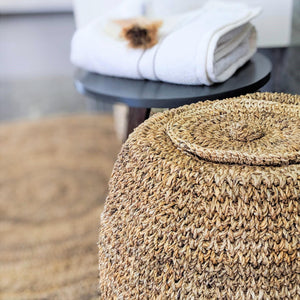 A dried banana fiber Laundry Hamper with a lid to cover the top. Natural golden brown in color. Set against a wild flower background.
