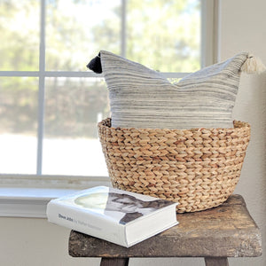 Throw pillow by Ginger Sparrow, a modern handcrafted home decor brand. The pillow features a soft ivory base with airy rugged stripes in black. Finished with fluffy black and white cotton tassels for some extra lush.