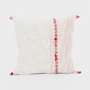 Throw pillows by Ginger Sparrow, a modern handcrafted home decor brand. A combination of ivory and terracotta red pillows stacked one on top the other. The pillow features a soft ivory base with airy geometric lines in teal and terracotta and finished with a row of fluffy marsala red cotton tassels for some extra lush.