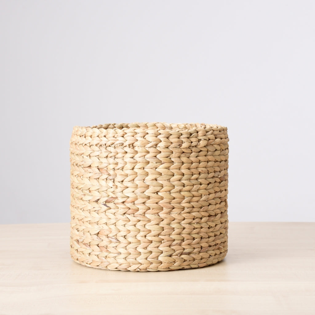 A set on watergrass baskets used as plant holders kept near a bench against a white wall.