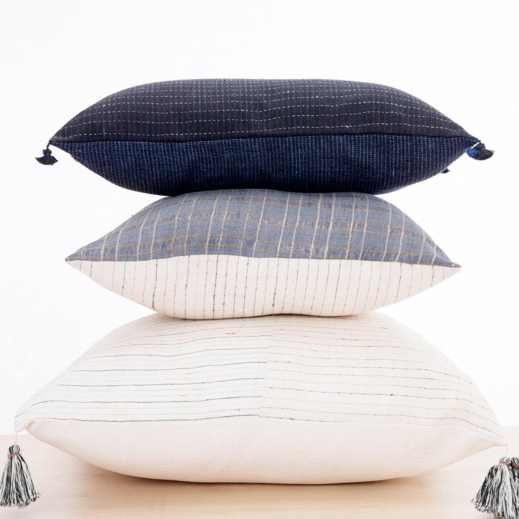 Two pillows stacked one on top of the other. One pillow is a small lumbar in 12 x20 inch and a black and indigo color. The other pillow is a soft ivory handwoven pillow in 22x22 inch size.