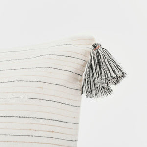 A soft ivory pillow in 22x22 inch size featuring fawn and indigo striped weave and lush corner tassels.