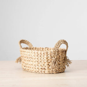 Closeup view of a dried water grass basket in a buttery golden hue, finished with braided handles. Perfect to stash fruits, towels, candles etc.