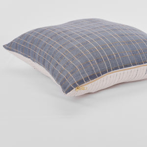 A combination of three stacked pillows in soft ivory, dusty blue and indigo palette.