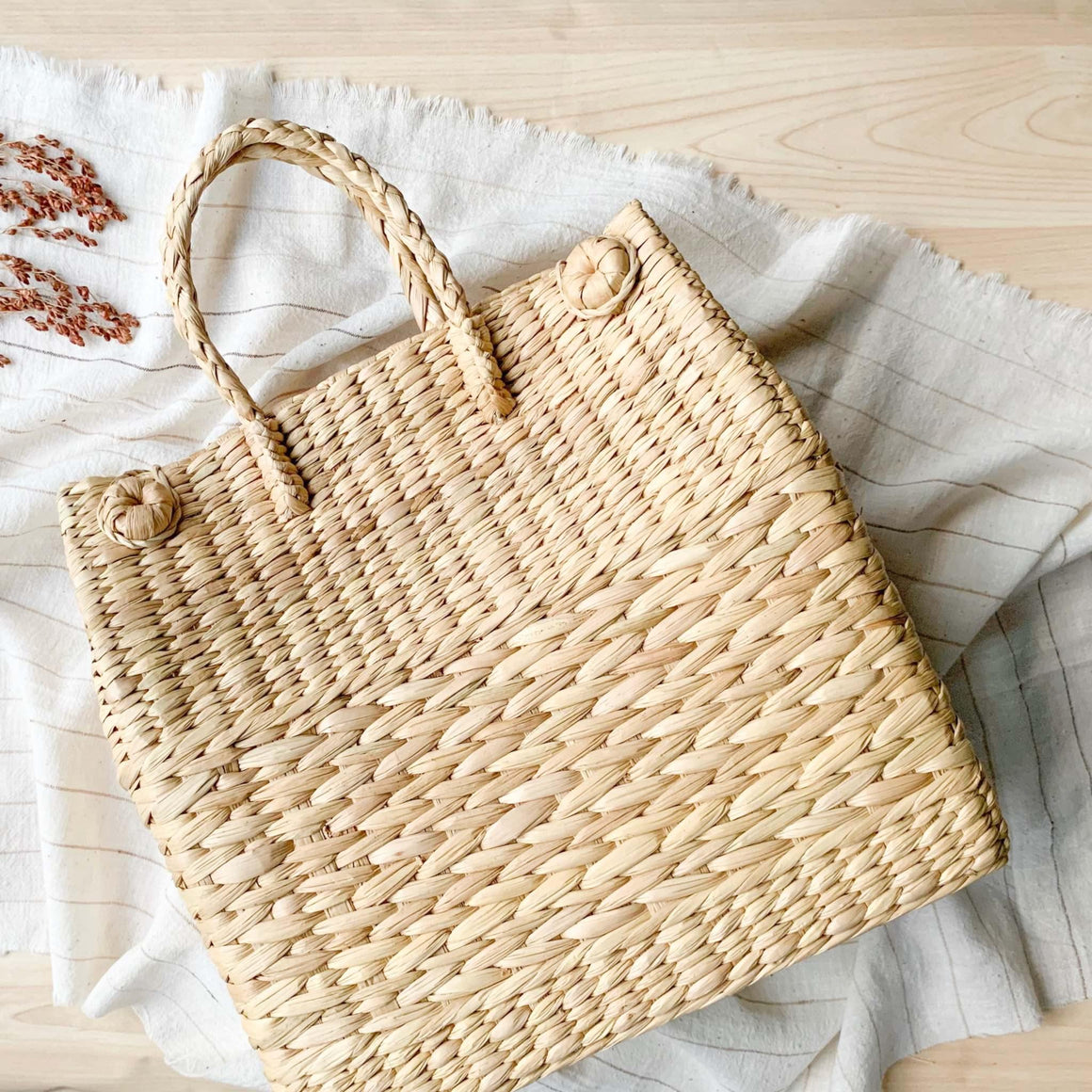 Watergrass Hamper Baskets in a light buttery golden hue. Handcrafted in 3 nesting sizes, great as a picnic hamper baskets. Crafted by Ginger Sparrow, a modern home decor brand.