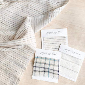 Handwoven cotton textiles by Ginger Sparrow, a modern handcrafted home decor brand. Featuring a soft ivory textile featuring fawn and indigo striped weave.
