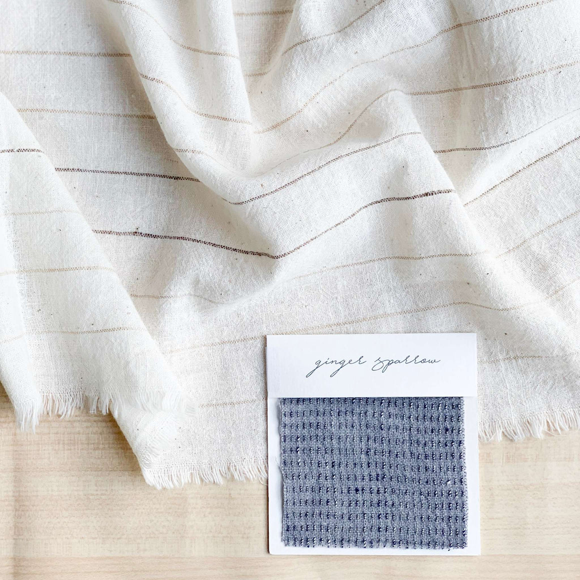A dusty blue throw pillow featuring an indigo striped weave. Handcrafted by Ginger Sparrow, a modern home decor brand.